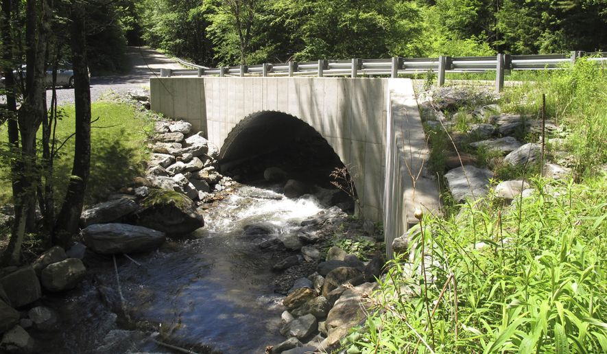 In this Wednesday, June 17, 2015 photo, a large culvert on the Crossett Brook in Duxbury, Vt., is being touted by experts as an example of a good culvert that allows the easy passage of fish and other wildlife in the stream. Water from a smaller nearby culvert falls about 3 feet from a pipe into the, river  making it impossible for fish and other wildlife to move upstream. Vermont is one of 13 Eastern states working to keep track of the often-unseen culverts, that despite their invisibility, are critical to wildlife habitat and minimizing flood damage. (AP Photo/Wilson Ring)