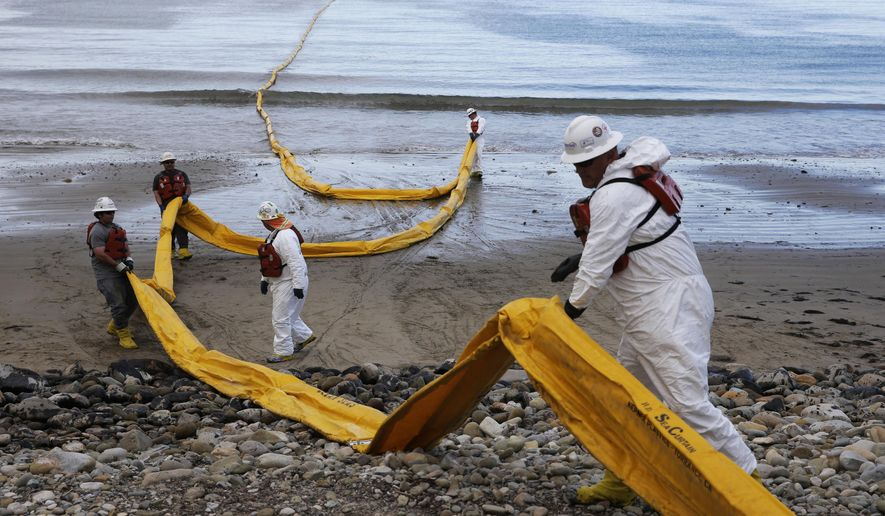 FILE - In this May 21, 2015 file photo, workers prepare an oil containment boom at Refugio State Beach, north of Goleta, Calif. Cleanup work continues one month after the May 19 oil spill north of Santa Barbara, Calif. The ruptured pipeline released up to 101,000 gallons of crude including 21,000 gallons that flowed into a storm drain and out into the Santa Barbara Channel.(AP Photo/Jae C. Hong, File)