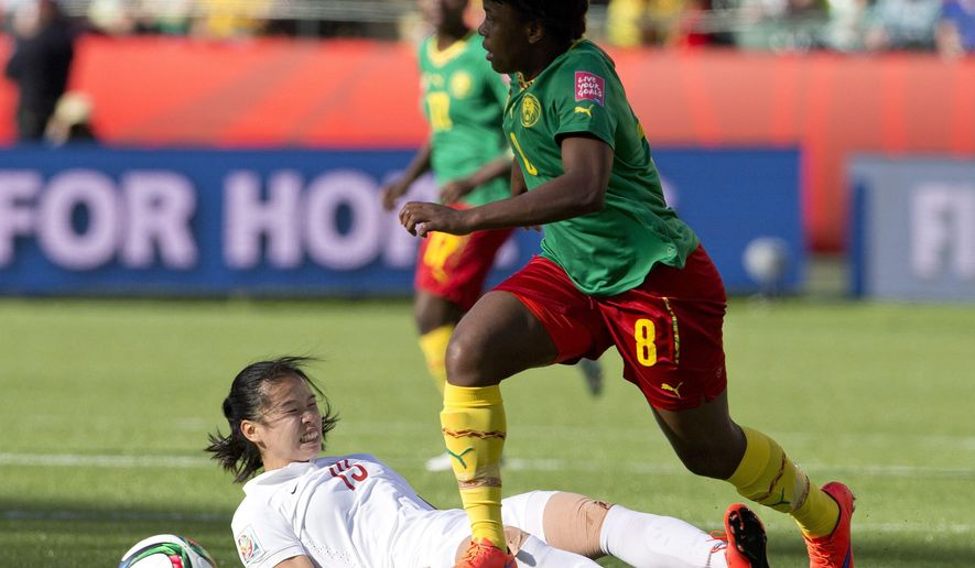 China's Tang Jiali (13) is knocked down by Cameroon's Raissa Feudjio (8) during second-half FIFA Women's World Cup soccer game action in Edmonton, Alberta, on Saturday, June 20, 2015. (Jason Franson/The Canadian Press via AP) MANDATORY CREDIT