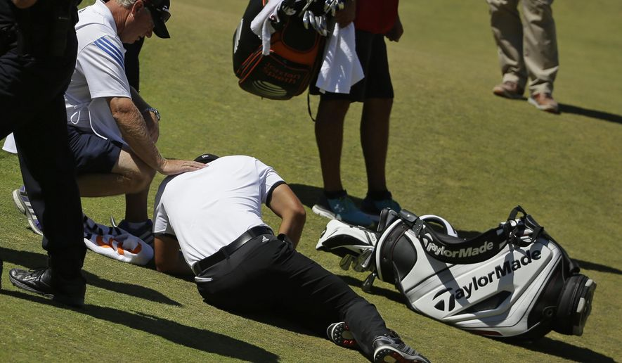 Jason Day, of Australia, lies in the fairway after falling down as his caddie Colin Swatton crouches beside him on the ninth hole during the second round of the U.S. Open golf tournament at Chambers Bay on Friday, June 19, 2015 in University Place, Wash. (AP Photo/Ted S. Warren)