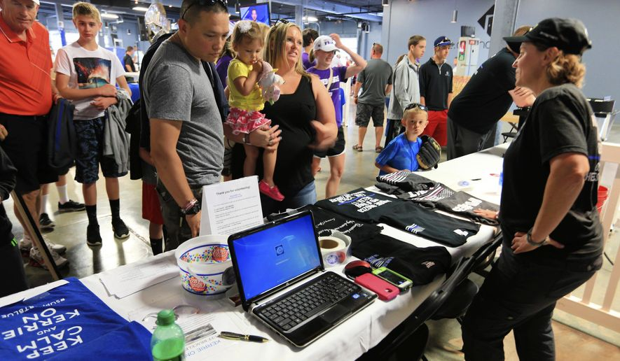 In this June 18, 2015, photo, John McNally of Lincoln, his daughter Katelynn, 2, and wife Heather look at T shirts for sale at the Support Blue booth outside TD Ameritrade Park in Omaha, Neb. The Support Blue campaign, that began as a way to show support for police officers, is now raising thousands of dollars for the causes championed by officer Kerrie Orozco, who was shot and killed in the line of duty last month. (AP Photo/Nati Harnik) (AP Photo/Nati Harnik)