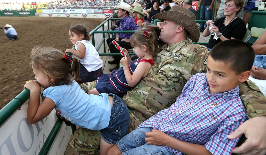 In this Friday, June 19, 2015 photo, Nevada Army National Guard Chief Warrant Officer Glen Spadin watches the rodeo action with his children after his surprise return from Afghanistan during Patriot Night ceremonies at the Reno Rodeo in Reno, Nev. Spadin returned after a year in Afghanistan to surprise his six children. (AP Photo/Cathleen Allison)