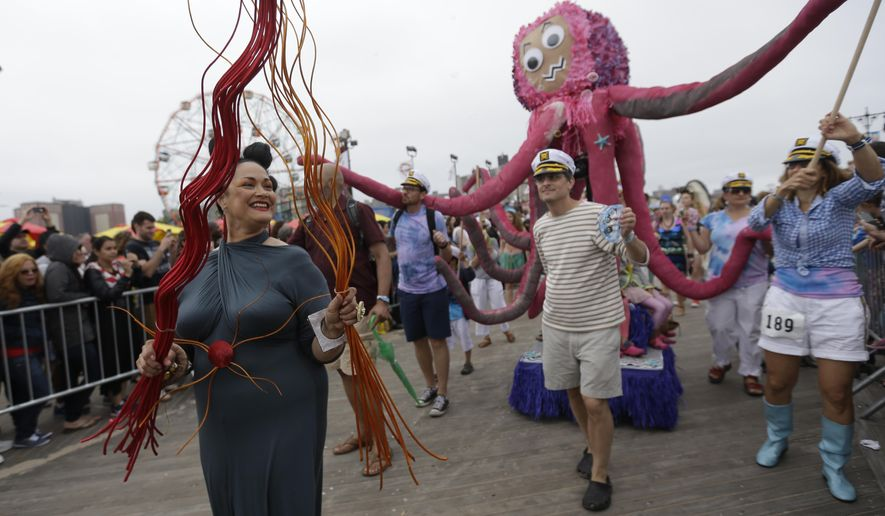 Participants march on the boardwalk during the 33rd annual Mermaid Parade in New York's Coney Island on Saturday, June 20, 2015. The parade began in 1983 and takes place on the Saturday closest to the first day of summer. (AP Photo/Mary Altaffer)