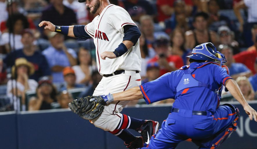 Atlanta Braves A.J. Pierzynski, left, scores past  New York Mets catcher Travis d'Arnaud on a Pedro Ciriaco base hit in the sixth inning inning of a baseball game Saturday, June 20, 2015, in Atlanta.  d'Arnaud  was shaken up up the play and left the game. (AP Photo/John Bazemore)