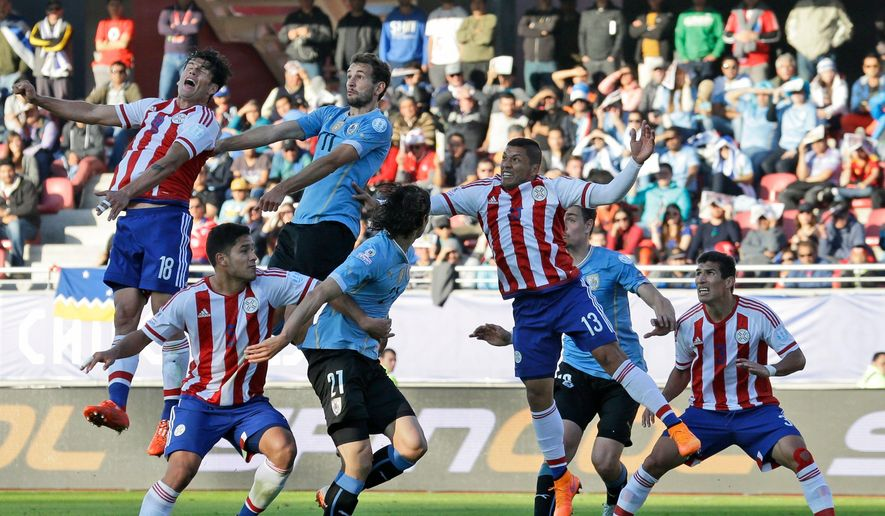 Paraguay's Nelson Haedo, top left, and Uruguay's Christian Stuani, top right, go for a header during a Copa America Group B soccer match at La Portada stadium in LaSerena, Chile, Saturday, June 20, 2015. (AP Photo / Luis Hidalgo)