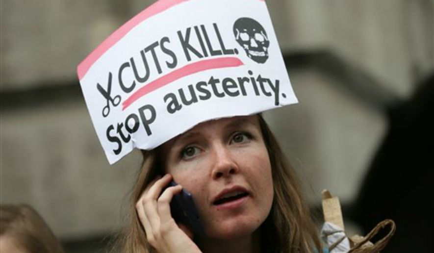 A demonstrator uses her phone outside the Bank of England during a protest against the Conservative Government and it's austerity policies in London, Saturday, June 20, 2015. The protest is intended to be peaceful, but demonstrators are angry at public sector cuts meant to address government deficits, which ballooned after Britain rescued troubled banks during the 2008 financial crisis. (AP Photo/Tim Ireland) ** FILE **