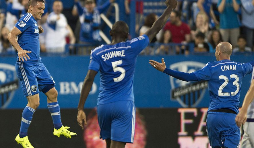 Montreal Impact's Donny Toia, left, celebrates with teammates Bakary Soumare (5) and Laurent Ciman (23) after scoring against Orlando City SC during first half MLS soccer action in Montreal, Saturday, June 20, 2015. (Graham Hughes(/The Canadian Press via AP) MANDATORY CREDIT