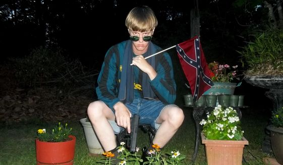 This undated image that appeared on Lastrhodesian.com, a website being investigated by the FBI in connection with Charleston, S.C., shooting suspect Dylann Roof, shows Roof posing for a photo while holding a Confederate flag. The website surfaced online Saturday, June 20, 2015, and also contained a hate-filled 2,500-word essay that talks about white supremacy and concludes by saying the author alone will need to take action. (Lastrhodesian.com via AP)