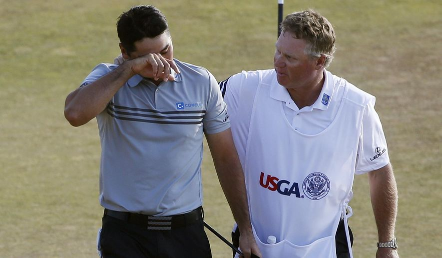 Jason Day, of Australia, left, walks off the 18th green with his caddie Colin Swatton after their third round of the U.S. Open golf tournament at Chambers Bay on Saturday, June 20, 2015 in University Place, Wash. (AP Photo/Lenny Ignelzi)