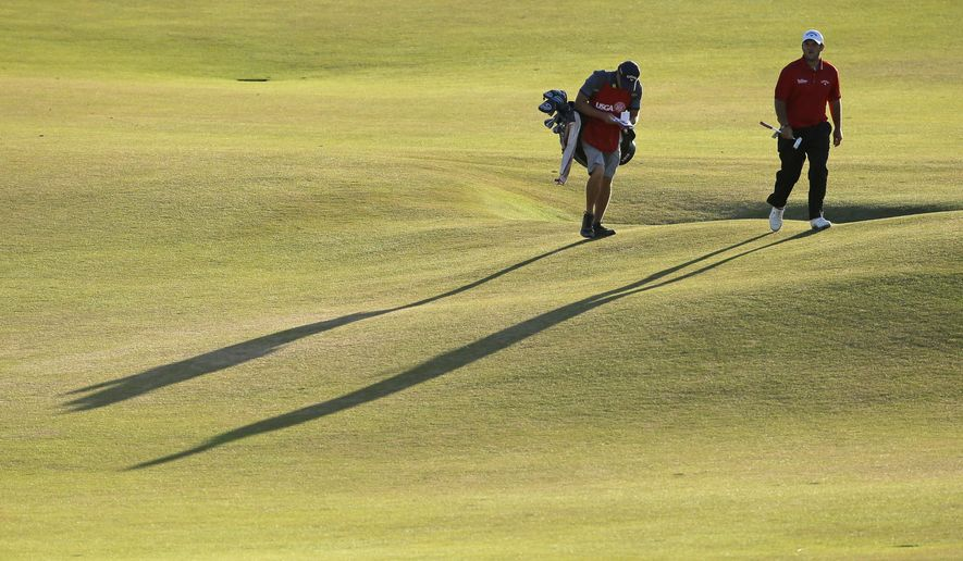 Patrick Reed, right, walks up the 18th fairway  during the second round of the U.S. Open golf tournament at Chambers Bay on Friday, June 19, 2015 in University Place, Wash. (AP Photo/Ted S. Warren)