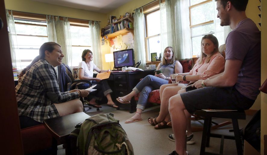In this photo taken Friday, June 12, 2015, at Camp Coniston directors and councilors meet  as they prepare to open for the summer season in Croyden, N.H.  As the summer camp season begins new state rules is New Hampshire require stronger background checks for everyone who gets the summer job. (AP Photo/Jim Cole)(AP Photo/Jim Cole)