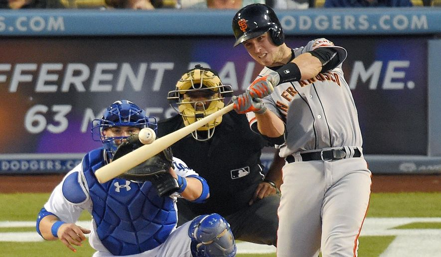 San Francisco Giants' Buster Posey, right, hits a grand slam as Los Angeles Dodgers catcher Yasmani Grandal, left, and home plate umpire Laz Diaz watch during the third inning of a baseball game, Friday, June 19, 2015, in Los Angeles. (AP Photo/Mark J. Terrill)