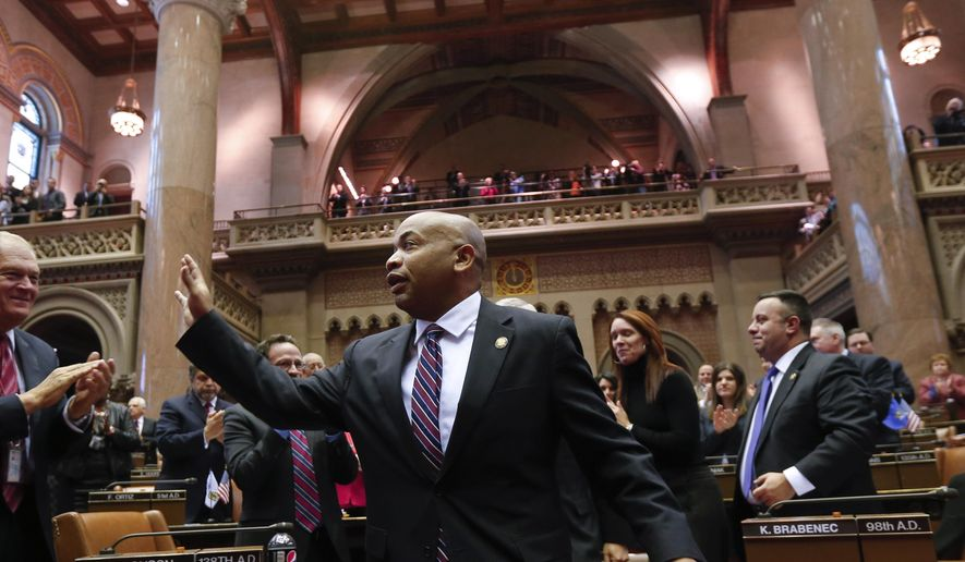 In this Feb. 3, 2015 file photo, newly-elected Assembly Speaker Carl Heastie, D-Bronx, waves to the Assembly after his election at the Capitol in Albany, N.Y. (AP Photo/Mike Groll, File)