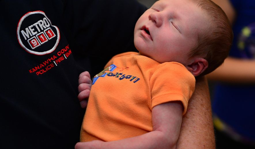 ADVANCE FOR MONDAY JUNE 21 AND THEREAFTER - In this Monday, June 15, 2015 photo, Debi Sutler, a Kanawha County Metro 911 dispatcher, holds Brayden Zane, the baby she helped deliver at the call center in Charleston, W.Va. .  Sutler talked Brooksan Huffman through childbirth over the phone on June 6.  Huffman and her family visited Sutler for the first time since the birth.   (Kenny Kemp/Charleston Gazette via AP)