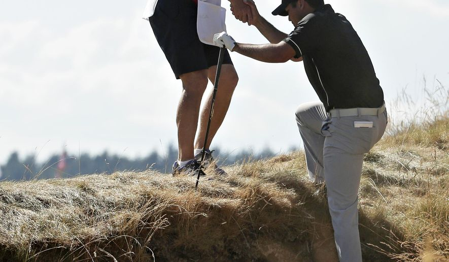 Jason Day, of Australia, gets a hand out of the bunker from his caddie Colin Swatton on the 10th hole during the final round of the U.S. Open golf tournament at Chambers Bay on Sunday, June 21, 2015 in University Place, Wash. (AP Photo/Charlie Riedel)