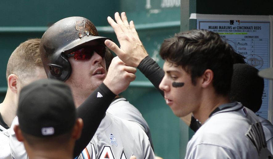Miami Marlins' Justin Bour, left, is congratulated in the dugout after he hit a solo home run off Cincinnati Reds starting pitcher Michael Lorenzen in the second inning of a baseball game, Sunday, June 21, 2015, in Cincinnati. (AP Photo/David Kohl)