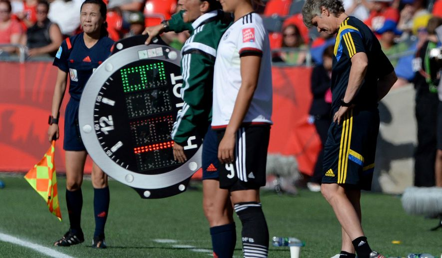 Sweden coach Pia Sundhage, right, looks down at the pitch as Germany forward Lena Lotzen (9) get ready to enter the game during the second half of a FIFA Women's World Cup soccer game in Ottawa, Ontario, on Saturday, June 20, 2015. (Sean Kilpatrick/The Canadian Press via AP) MANDATORY CREDIT