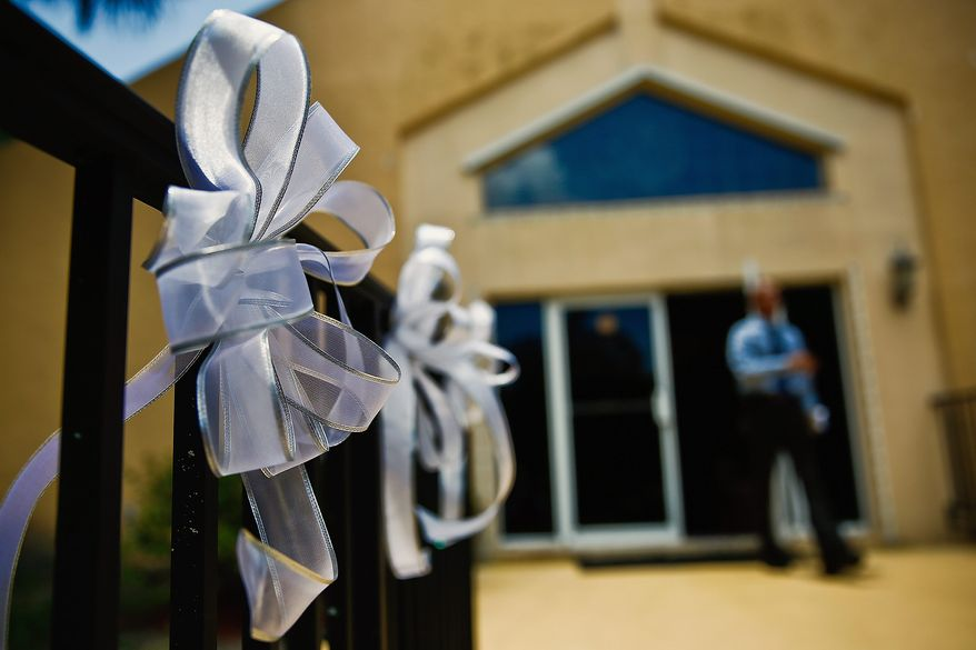 Mourners placed ribbons in memory of the nine people killed at the Emmanuel AME Church in Charleston, South Carolina, last Wednesday. The incident has renewed passions on all sides of the debate on gun rights and concealed carry laws. (associated press)