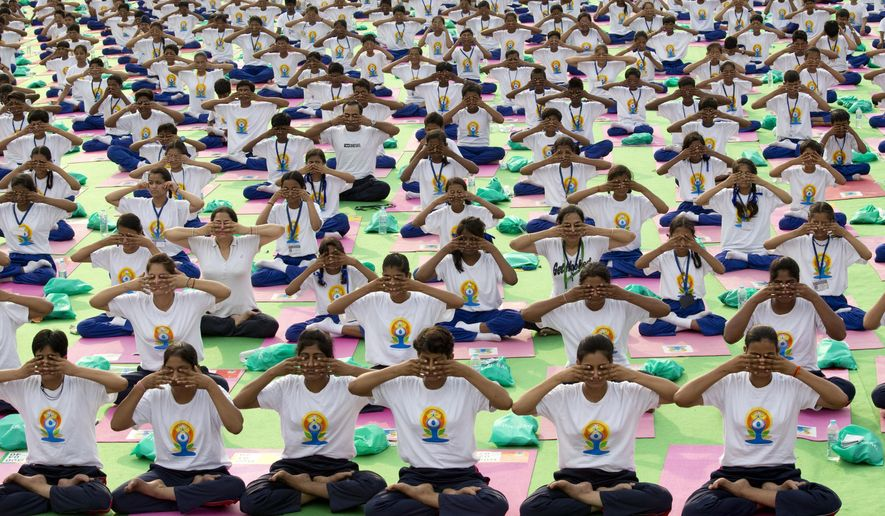 Indians perform yoga on Rajpath, in New Delhi, India, Sunday, June 21, 2015. Millions of yoga enthusiasts are bending their bodies in complex postures across India as they take part in a mass yoga program to mark the first International Yoga Day. (AP Photo/ Manish Swarup)