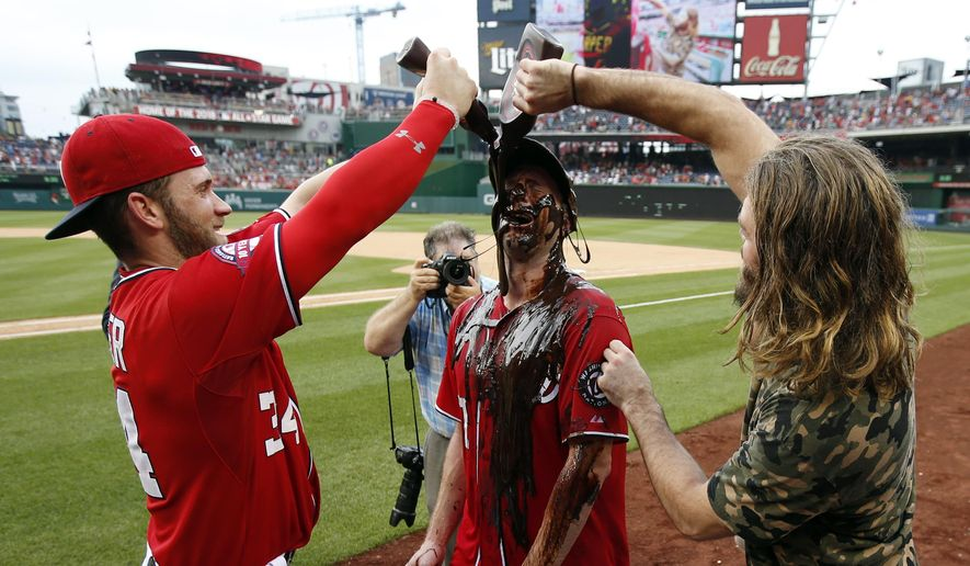 Washington Nationals' Bryce Harper, left, and Jayson Werth, right, douse starting pitcher Max Scherzer with chocolate syrup after Scherzer's no-hitter baseball game against the Pittsburgh Pirates at Nationals Park, Saturday, June 20, 2015, in Washington. The Nationals won 6-0. (AP Photo/Alex Brandon)