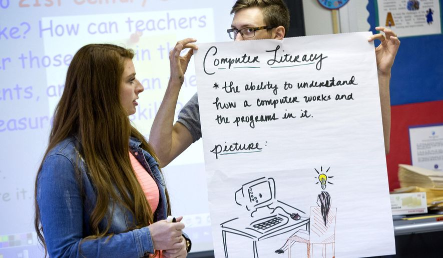Rebecca Diggs, left, and Jacob Griffin, holding a poster while they and Hyejin Ra (not pictured) present their Computer Literacy topic to fellow students in Carrie Gantt's Teachers for Tomorrow class on Wednesday, May 27, 2015 at Princess Anne High School in Virginia Beach, Va. A recent study shows that fewer students want to become teachers. To combat this decline, Virginia Beach offers a state program, Teachers for Tomorrow. (The' N. Pham/The Virginian-Pilot via AP)