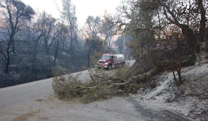 A fire truck moves past a downed tree on Las Piletas Road, Sunday, June 21, 2015, in Santa Margarita, Calif. A fast-moving fire that broke out near Santa Margarita, about 10 miles northeast of San Luis Obispo, Saturday afternoon forced the evacuation of several hundred residents, the San Luis Obispo Tribune reported. (David Middlecamp/The Tribune via AP)