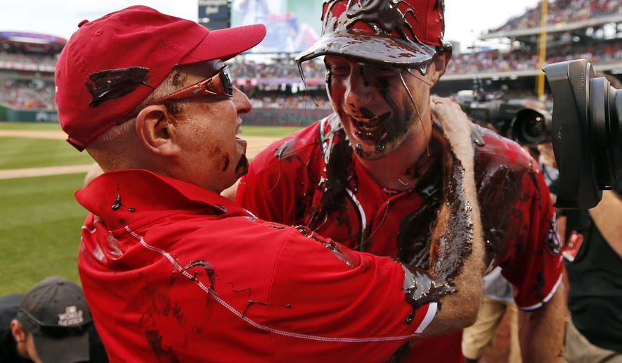 Washington Nationals owner Mark Lerner, left, embraces Washington Nationals starting pitcher Max Scherzer, who is covered with chocolate syrup, after Scherzer's no-hitter baseball game against the Pittsburgh Pirates at Nationals Park, Saturday, June 20, 2015, in Washington. The Nationals won 6-0. (AP Photo/Alex Brandon)