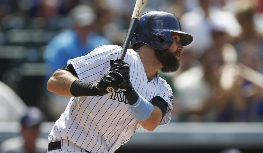 Colorado Rockies' Charlie Blackmon follows the flight of his single to drive in two runs off Milwaukee Brewers starting pitcher Matt Garza in the fourth inning of a baseball game Sunday, June 21, 2015, in Denver. (AP Photo/David Zalubowski)