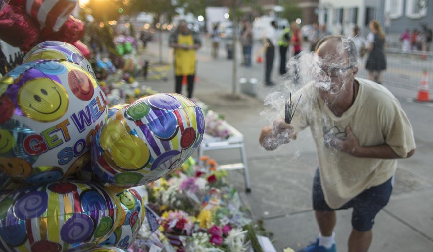 Raymond Smith of Charleston uses incense to spiritually cleanse the front of the Emanuel AME Church Sunday, June 21, 2015, before the first worship service since nine people were fatally shot at the church during a Bible study group, in Charleston, S.C. (AP Photo/Stephen B. Morton)