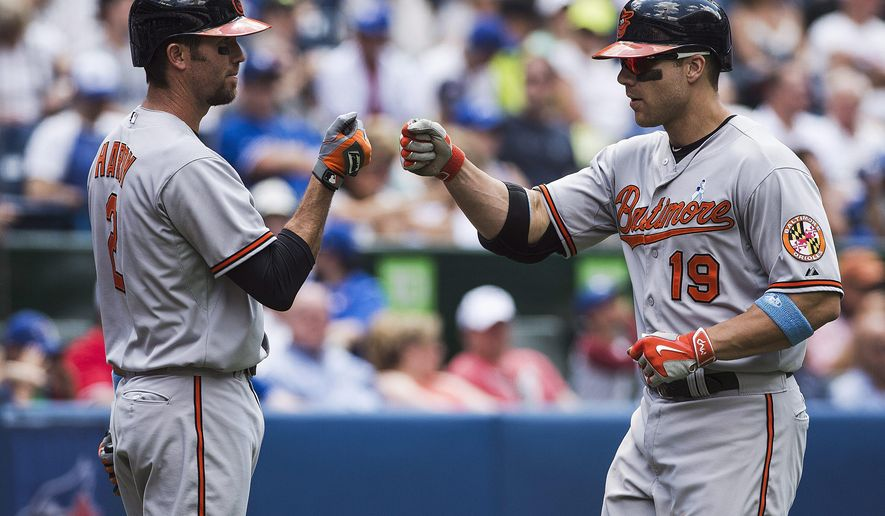 Baltimore Orioles Chris Davis, right, celebrates his solo home run against the Toronto Blue Jays with J.J. Hardy during the fifth inning of a baseball game in Toronto, Sunday, June 21, 2015. (Aaron Vincent Elkaim/The Canadian Press via AP)