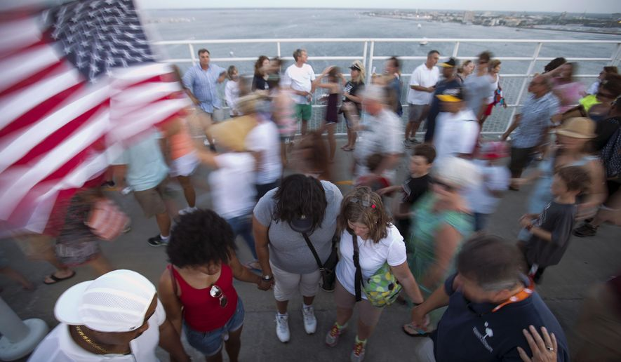 People join hands in prayer as thousands of marchers meet on Charleston's main bridge in a show of unity after nine black church parishioners were gunned down during a Bible study, Sunday, June 21, 2015, in Charleston, S.C. (AP Photo/David Goldman)
