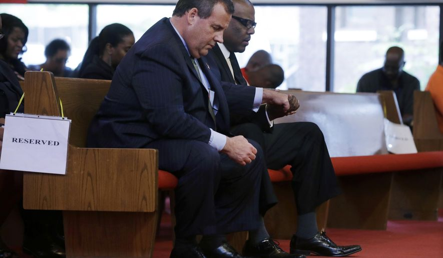 New Jersey Gov. Chris Christie, left,  and Dwayne D. Warren, Mayor of Orange, N.J., hold hands during a service at St. Matthew African Methodist Episcopal Church Sunday, June 21, 2015, in Orange, N.J. The service offered prayers and thoughts of the nine people who were killed at Emmanuel AME Church in Charleston, SC, last Wednesday. (AP Photo/Mel Evans)