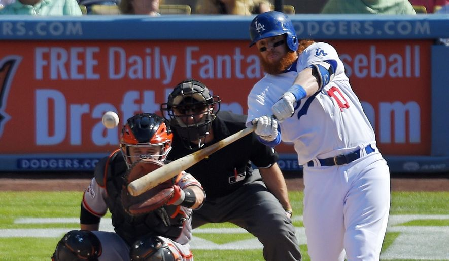 Los Angeles Dodgers' Justin Turner, right, hits a solo home run as San Francisco Giants catcher Buster Posey, left, and home plate umpire Chris Guccione, center, watch during the first inning of a baseball game, Saturday, June 20, 2015, in Los Angeles. (AP Photo/Mark J. Terrill)