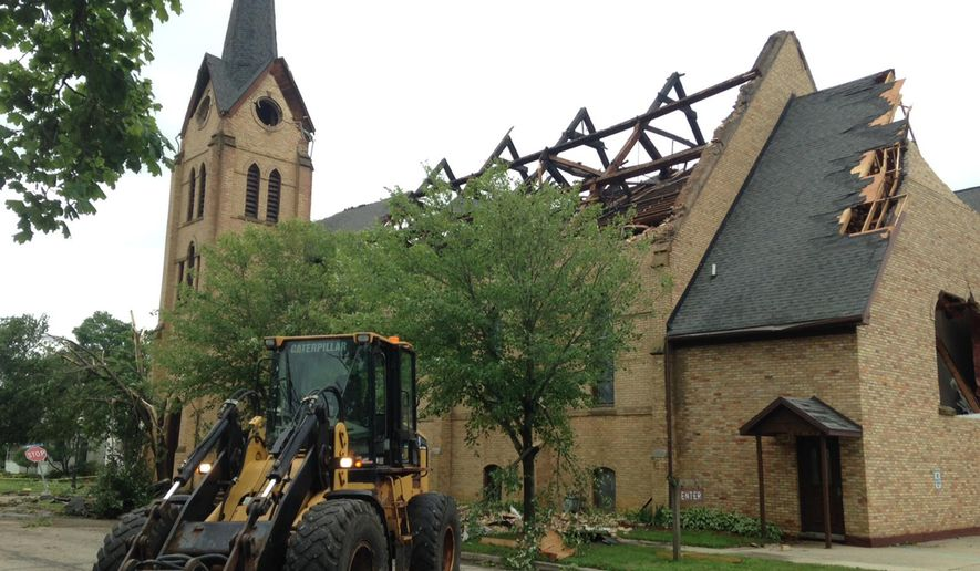 Downed trees and a damaged roof are seen on the Portland United Methodist Church that was damaged Monday, June 22, 2015, in Portland, Mich. Five people were rescued from damaged buildings in Portland and thunderstorms packing strong winds caused damage in Iowa and Illinois as severe weather swept through parts of the Midwest on Monday. (Rod Sanford/Lansing State Journal via AP)