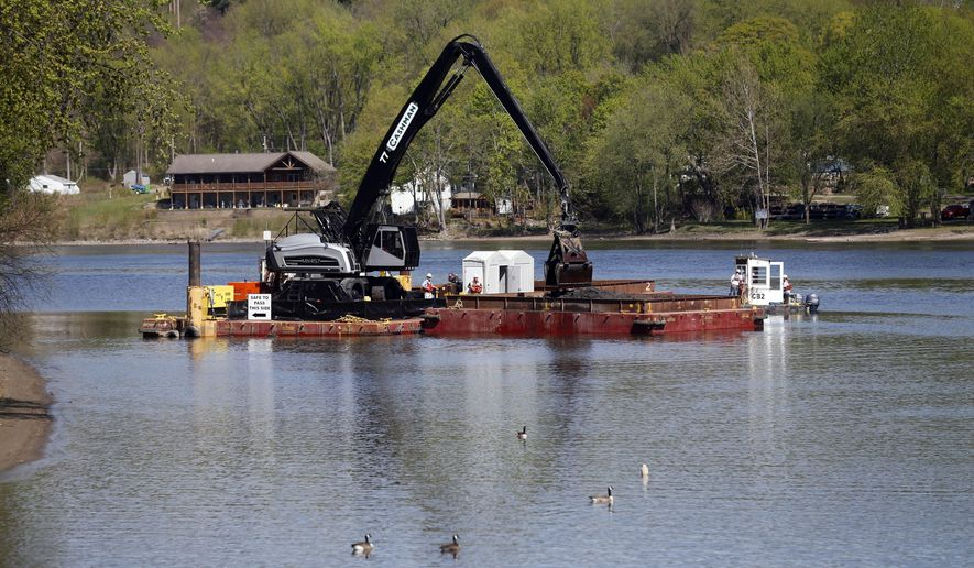 FILE - In this May 7, 2015, file photo, crews perform dredging work along the upper Hudson River in Waterford, N.Y. Long after the last dredging barge leaves the upper Hudson River, scientists will track the slow fade in contamination levels. General Electric Co. expects to finish this year removing some 2.7 million cubic yards of contaminated river sediment under its landmark Superfund agreement with the federal Environmental Protection Agency. After six years of digging, crews will have removed most of the PCBs on the river bottom discharged decades ago from two GE plants upriver. (AP Photo/Mike Groll, File)
