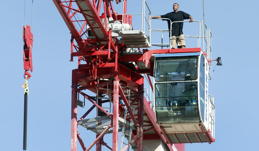 A unidentified man described stands on top of  the cab of a high-rise crane at a construction site near City Hall in San Jose, Calif.,  Monday June 22, 2015. The man climbed into the crane, which was 90 feet above the street, Sunday night. He was shouting messages about homelessness and sharing with listeners the unhappiness he felt about his situation. (Karl Mondon/Bay Area News Group via AP)