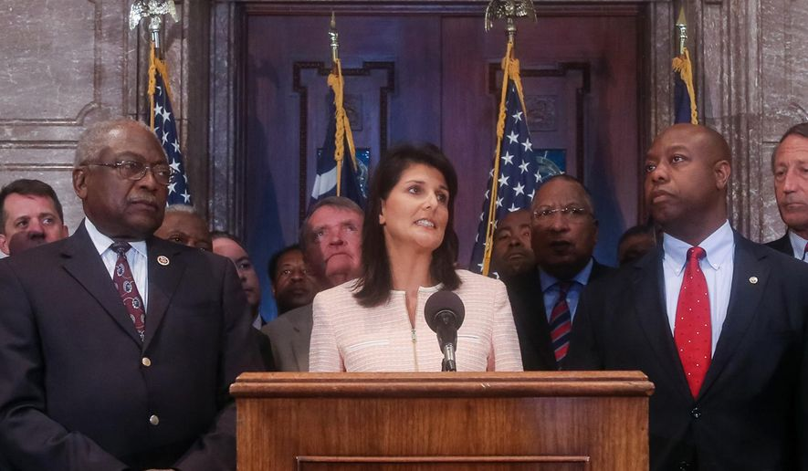 South Carolina Gov. Nikki Haley speaks during a news conference in the South Carolina State House, Monday, June 22, 2015, in Columbia, S.C. Haley said that the Confederate flag should come down from the grounds of the state capitol, reversing her position on the divisive symbol amid growing calls for it to be removed. Also pictured are U.S. Congressman James Clyburn, left, and U.S. Sen. Tim Scott, right. (Tim Dominick/The State via AP)