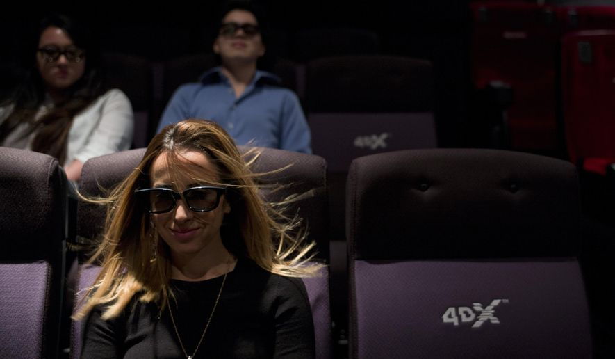 In this Wednesday, May 20, 2015 photo, a wind effect is demonstrated on marketing director Yassamine Wahab at the CJ's 4DX Lab in the Hollywood Section of Los Angeles. With domestic movie theater attendance stagnant in recent years, more theater owners are looking to provide immersive jolts to goose both moviegoers and box office revenues. (AP Photo/Jae C. Hong)