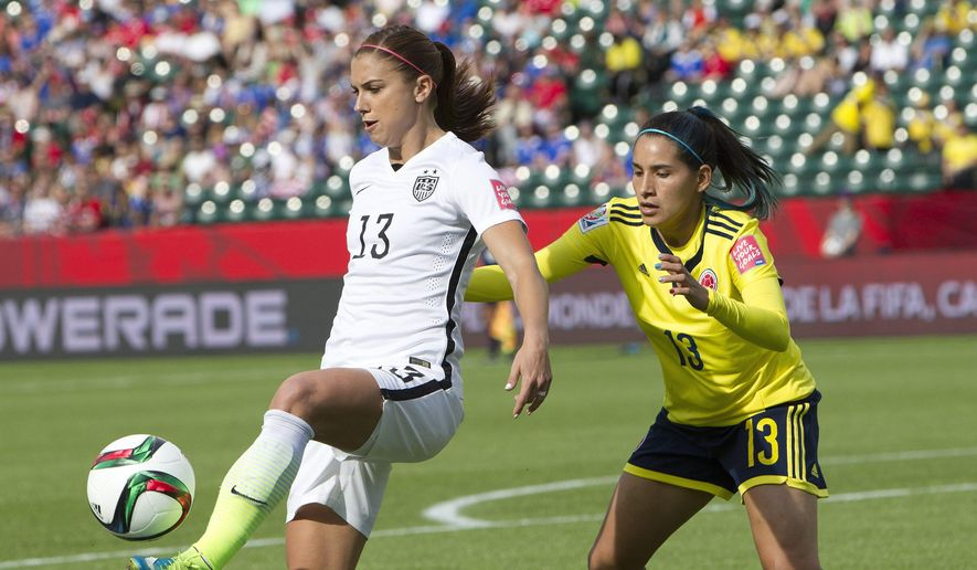 United States' Alex Morgan (13) kicks the ball in front ofColombia's Angela Clavijo (13) during first half FIFA Women's World Cup round of 16 action in Edmonton, Alberta, Canada, Monday, June 22, 2015.  (Jason Franson/The Canadian Press via AP) MANDATORY CREDIT
