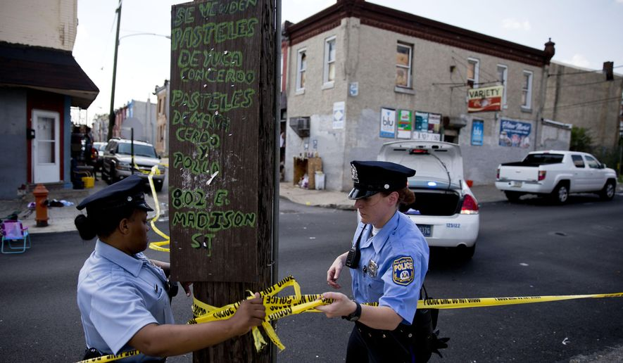 Police officers secure a crime scene Monday, June 22, 2015, in Philadelphia. Police say several people have been injured in the second shooting of a group of people in Philadelphia in three days. A police spokeswoman says the gunfire occurred at about 2:30 p.m. Monday on a street in the Kensington section of the city. (AP Photo/Matt Rourke)