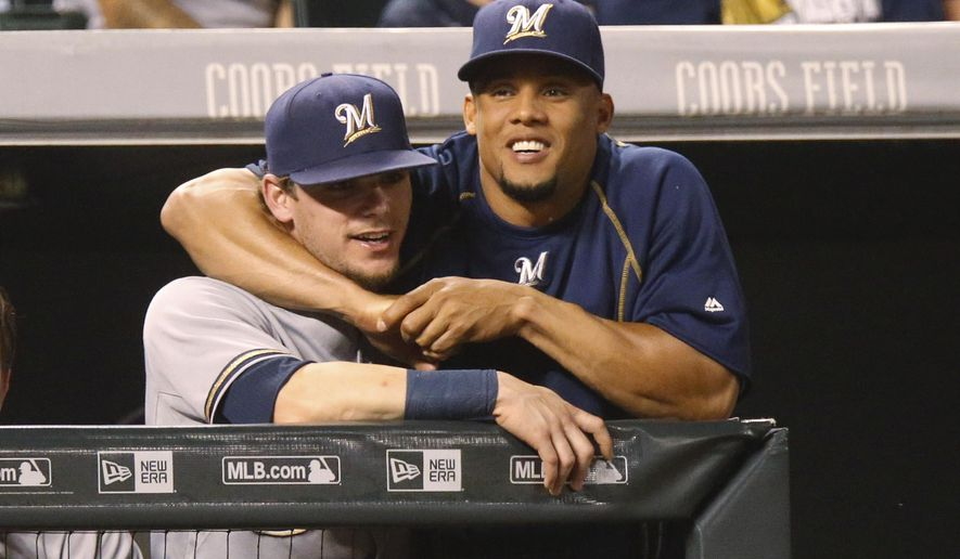 Milwaukee Brewers' Carlos Gomez, right, jokes with second baseman Scooter Gennett as they lean over the dugout rail to watch the Colorado Rockies in the seventh inning of a baseball game Friday, June 19, 2015, in Denver. Milwaukee won 9-5. (AP Photo/David Zalubowski)
