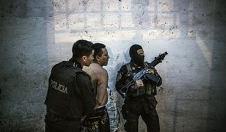 In this May 28, 2015 photo, members of the fast response police units, known as Halcones, detain a suspected gang member, who was found out of breath on a bed following a chase by police, in San Salvador, El Salvador. Observers blame the worsening insecurity on the breakdown of a 1.5-year-old truce between the gangs and the government. While the homicide rate plunged, critics say the truce gave the gangs time to strengthen, train and acquire heavier arms than they had in the past. (AP Photo/Manu Brabo)