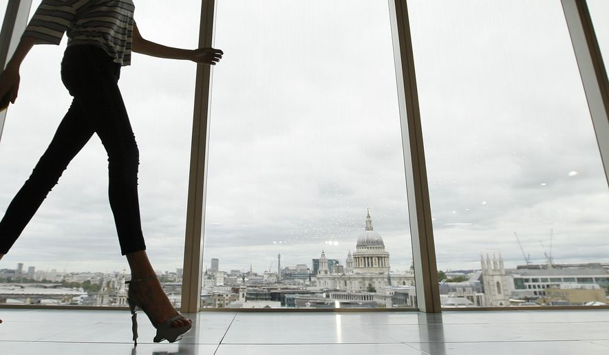 FILE - In this Sunday, Sept. 16, 2012 file photo, a model walks past a window with a view of St Paul's Cathedral during the presentation of the Matthew Williamson Spring/Summer 2013 collection at London Fashion Week. Doctors in Australia report that a 35-year-old woman was hospitalized for four days after experiencing muscle damage, swelling, and nerve blockages in her legs after squatting for several hours while wearing tight-fitting denims. (AP Photo/Alastair Grant, File)