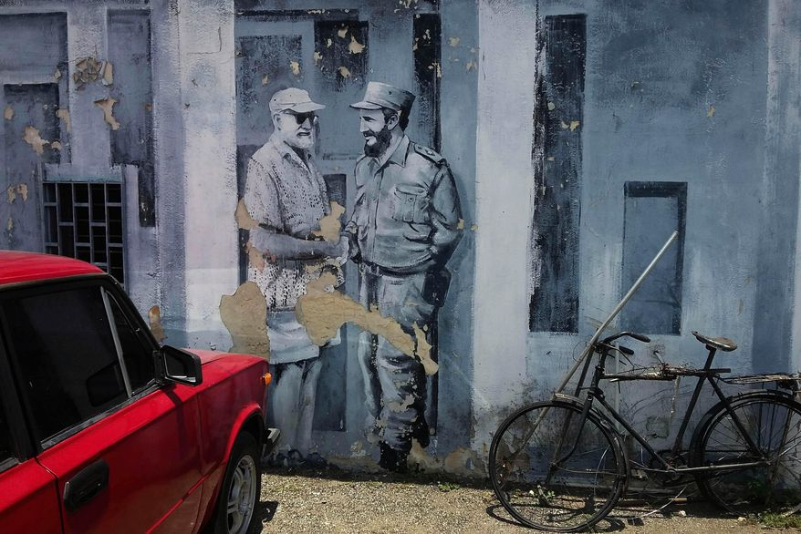 A mural of author Ernest Hemingway and Fidel Castro shaking hands covers a downtown parking lot in Havana, Cuba, Monday, June 22, 2015. Cuban architects, engineers and workmen will construct a two-story laboratory where thousands of photos, books and letters to and from Hemingway can be treated and preserved. (AP Photo/Ramon Espinosa)