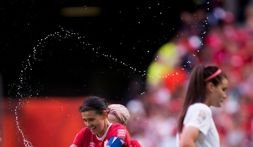 Canada's Christine Sinclair, left, sprays water in celebration as Switzerland's Rahel Kiwic, right, leaves the field after Canada defeated Switzerland 1-0 in the FIFA Women's World Cup round of 16 soccer action in Vancouver, British Columbia, Canada, on Sunday, June 21, 2015 . (Darryl Dyck/The Canadian Press via AP) MANDATORY CREDIT
