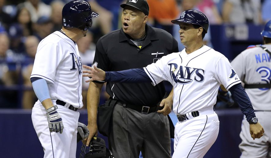 Tampa Bay Rays third base coach Charlie Montoyo, right, restrains Asdrubal Cabrera, left, as he argues a called strike with home plate umpire Kerwin Danley during the fifth inning of a baseball game against the Toronto Blue Jays Monday, June 22, 2015, in St. Petersburg, Fla.  Cabrera was ejected. (AP Photo/Chris O'Meara)