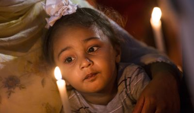 In this Tuesday, Aug. 7, 2012, file photo, a child looks at a candle during a vigil at the Oak Creek Civic Center in Oak Creek, Wis., for the victims of a mass shooting at the Sikh Temple of Wisconsin. (AP Photo/Tom Lynn)