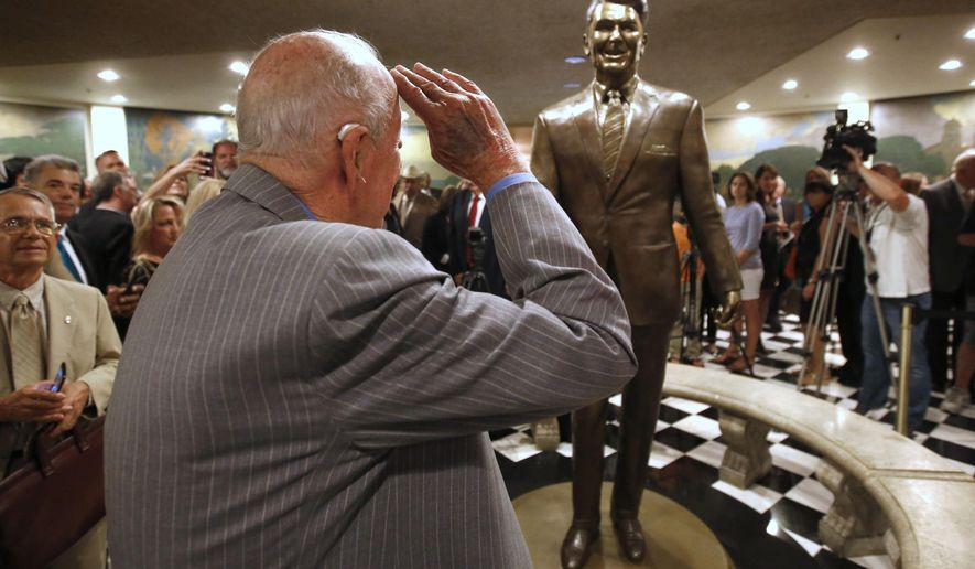 Former Secretary of State George Shultz salutes a statue of his former boss, President Ronald Reagan, that was unveiled at the Capitol in Sacramento, Calif., Monday, June 22, 2015.  The 8-foot-tall bronze  statue of California's 33rd governor and the 40th President of the United States was created by sculptor Douglas Van Howd and is on display in the basement the state Capitol rotunda. (AP Photo/Rich Pedroncelli)