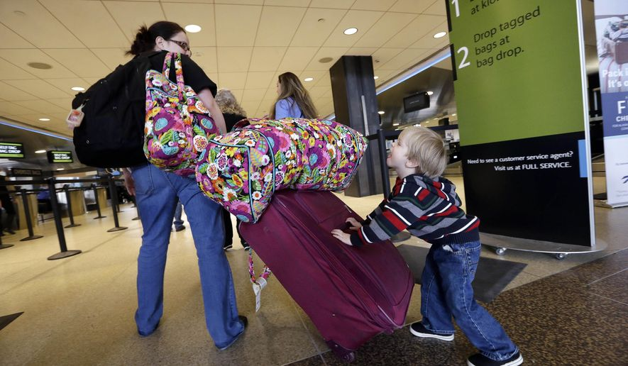 In this photo taken Tuesday, March 24, 2015, Colin Drummond, 4, pushes luggage from behind as he walks with family members to check-in a relative for an Alaska Airlines flight at Seattle-Tacoma International Airport in SeaTac, Wash. U.S. airlines continue to collect record fees from passengers who check suitcases or make changes to their reservations, according to data released Monday, June 22, 2015 by the Bureau of Transportation Statistics. (AP Photo/Elaine Thompson)