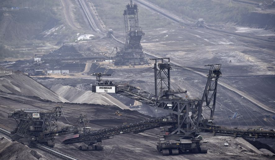 FILE- In this April 3, 2014, file photo, giant machines dig for brown coal at the open-cast mining Garzweiler near the city of Grevenbroich, western Germany. A global health commission organized by the prestigious British medical journal Lancet recommended in a report published Monday, June 22, 2015, substituting cleaner energy worldwide for coal will reduce air pollution and give Earth a better chance at avoiding dangerous climate change. (AP Photo/Martin Meissner, File)